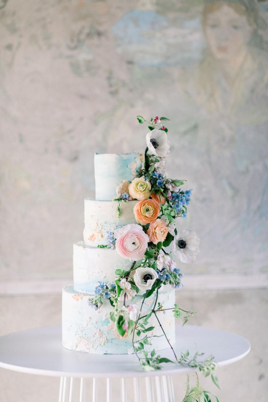 Romantic spring pastel buttercream wedding cake in pale blue and peach with cascading fresh flowers and greenery | Photography: Kate Preftakes via Style Me Pretty
