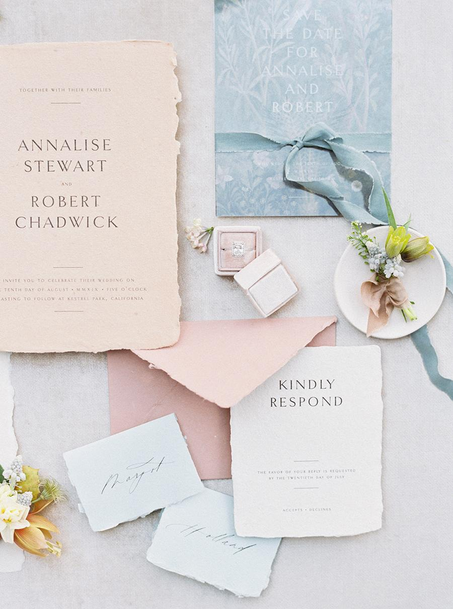 Spring pastel wedding invitation suite in pale blue, blush pink and peach with torn edge paper and fine black lettering | Photography: Anya Kernes via Style Me Pretty