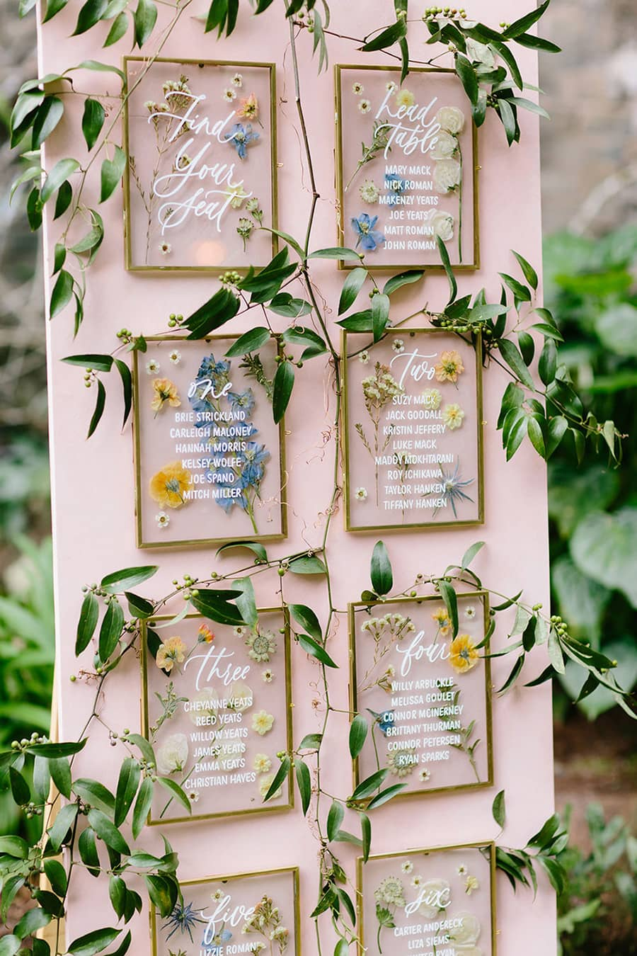 Spring pastel wedding reception seating chart featuring a blush pink backdrop, gold frames, pressed flowers and trailing greenery | Photography: Melia Lucida via 100 Layer Cake