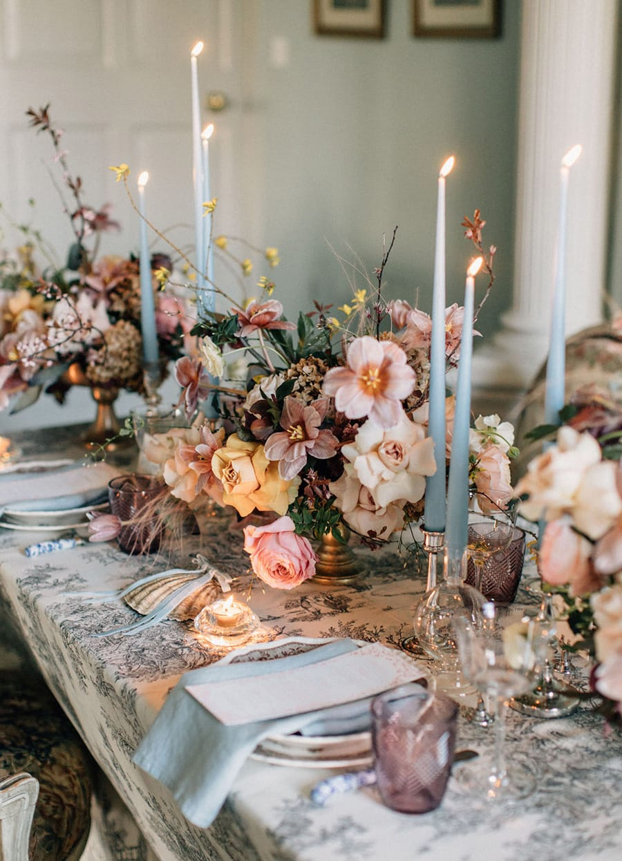 Romantic spring pastel wedding reception table setting featuring pale blue taper candles and napkins, purple glassware and rambling floral arrangements in gold footed vases atop a vintage patterned tablecloth | Photography: Melia Lucida via 100 Layer Cake