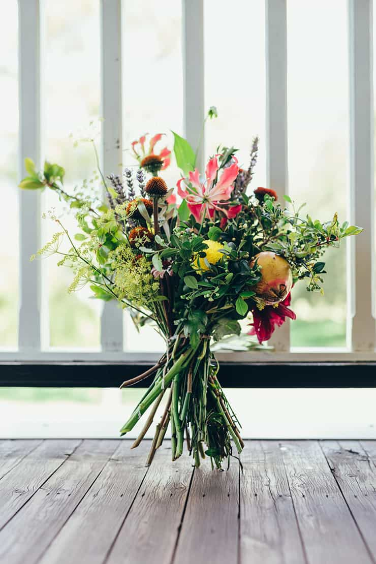 Wild green and red wedding bouquet with fruit