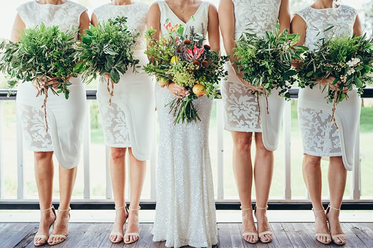 Bridesmaids wearing stylish white lace cocktail dresses with greenery bouquets
