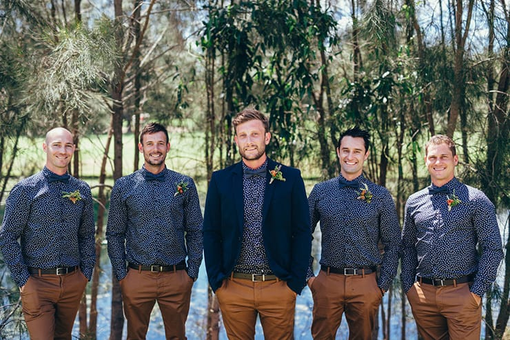 Groomsmen wearing navy patterned shirt, bow tie and brown slacks
