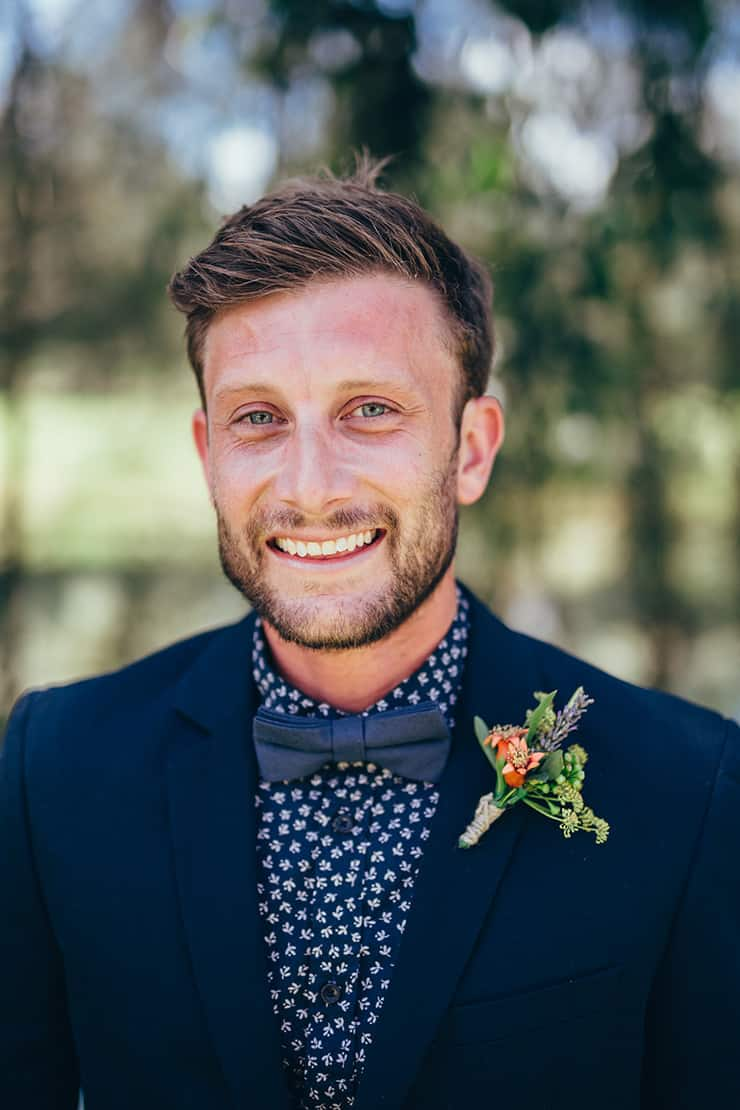 Navy groom suit with patterned shirt and bow tie