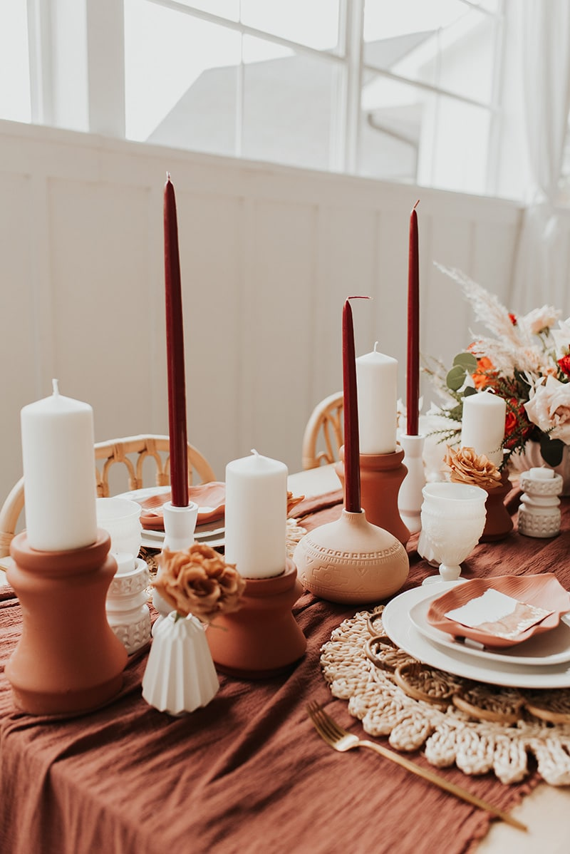 Romantic Boho Terracotta Wedding Ideas | An earthy boho wedding reception table with rattan dining chairs features alternating terracotta and white candles in ceramic candle holders of different shapes and sizes on a terracotta cheesecloth table runner alongside brass cutlery, natural woven placemats and layered white plateware topped with a leaf shaped ceramic dish and torn edge paper place card. | Photography: Bruna Kitchen