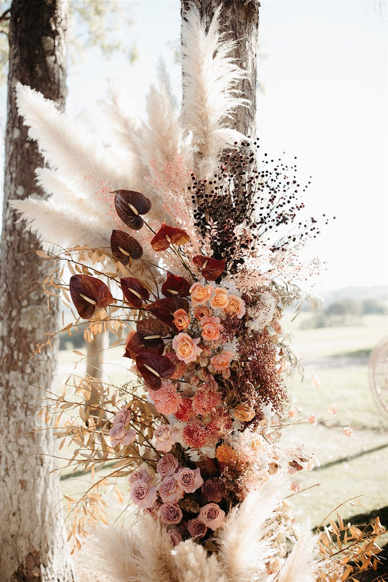 Romantic Boho Terracotta Wedding Ideas | Wild boho wedding ceremony floral pillar featuring merlot anthurium, peach and lilac roses, pink chrysanthemum disbuds and sprays of purple stirlingia, pale pink ruscus, neutral pampas grass and dried foliage. | Photography: Carly Tia via Hello May