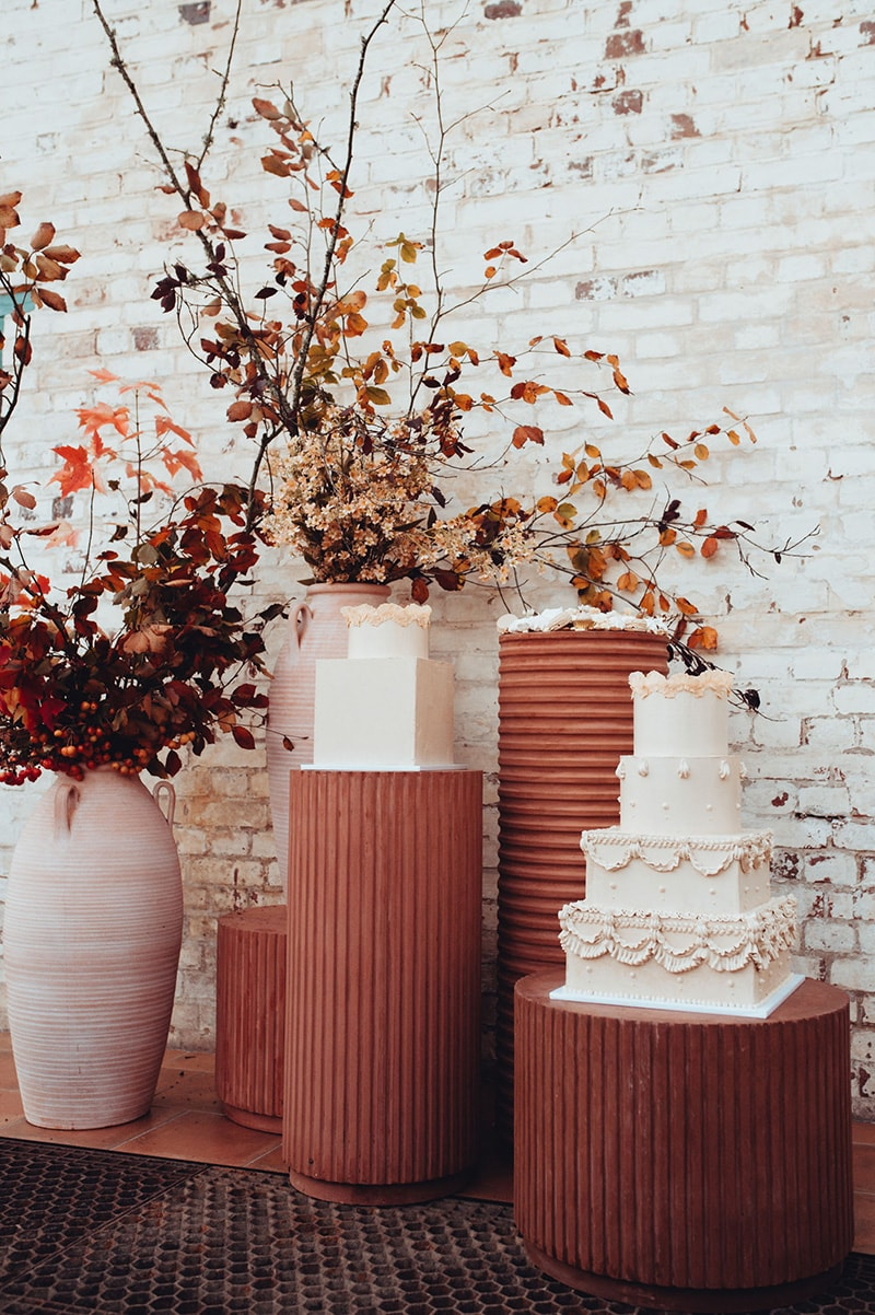 Romantic Boho Terracotta Wedding Ideas | A trio of white wedding cakes sits atop round corrugated terracotta plinths in different heights and diameters alongside tall white ceramic urns filled with autumnal dried foliage in front of a white worn brick wall. | Photography: Chelsea White Photography via Green Wedding Shoes