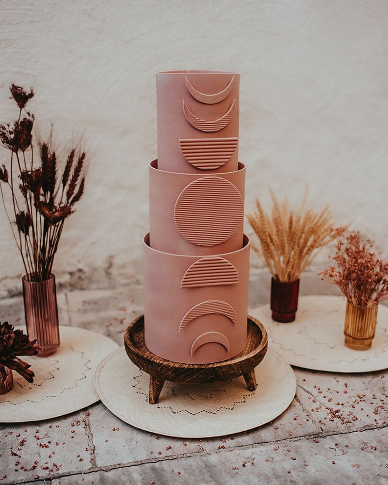 Romantic Boho Terracotta Wedding Ideas | Three tier matte pink terracotta fondant wedding cake featuring moon phases from top to bottom in corrugated texture. The cake is displayed on a carved wooden stand and surrounded by dried flowers in ribbed glass vases. | Photography: Kuenzli Photography via Rock My Wedding