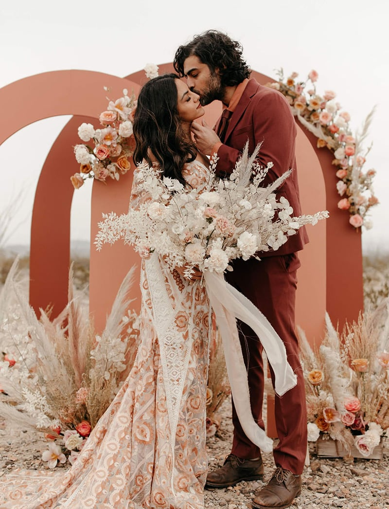 Romantic Boho Terracotta Wedding Ideas | A trio of terracotta and clay wedding ceremony arches in a desert landscape decorated with neutral, peach, pink and white flowers. A couple stands in front of the ceremony backdrop. The bride wears a terracotta coloured wedding dress with bold lace detail holding a bouquet featuring a spray of blush and white flowers and trailing white ribbons. The groom wears a dark terracotta suit and tie with dusty orange shirt and brown leather shoes as he caresses his bride's face and kisses her on the cheek. | Photography: Melissa Marshall via Green Wedding Shoes