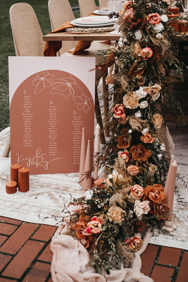 Romantic Boho Terracotta Wedding Ideas | Boho wedding reception table styling with a lush floral garland featuring tulips, orchids, roses and carnations in earthy tones that cascades onto the floor alongside clusters of clay and rust coloured pillar candles and an arch shaped terracotta seating chart with fine line floral illustrations and guest names in white ink. | Photography: Will and Co via Wedshed