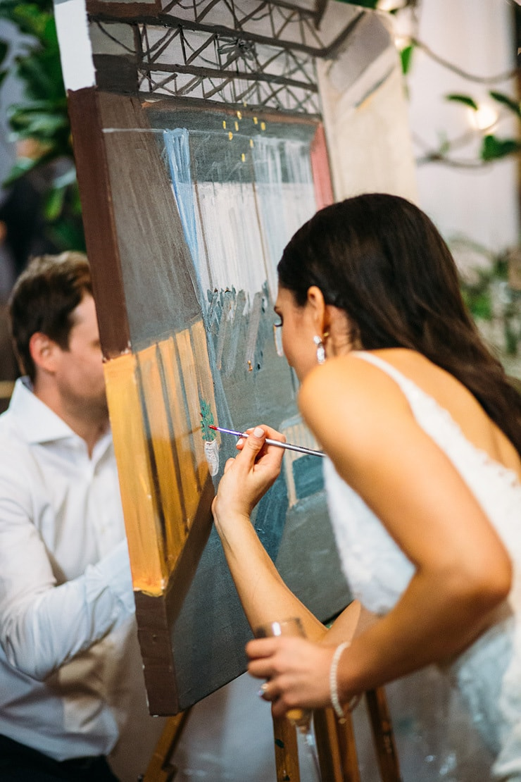 Guests painting wedding scene on canvas | Wildflower Weddings