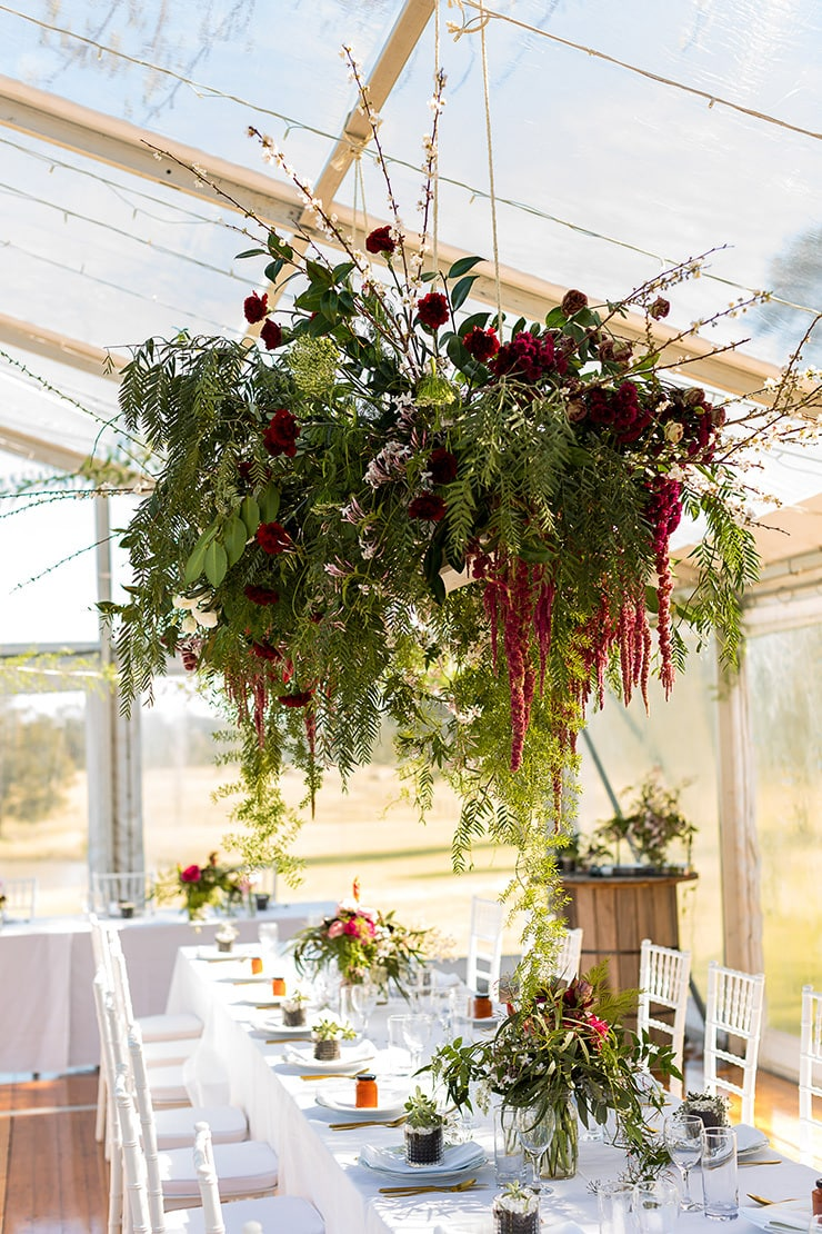 Rustic farm marquee wedding reception with burgundy flowers | Gemma Clarke Photography