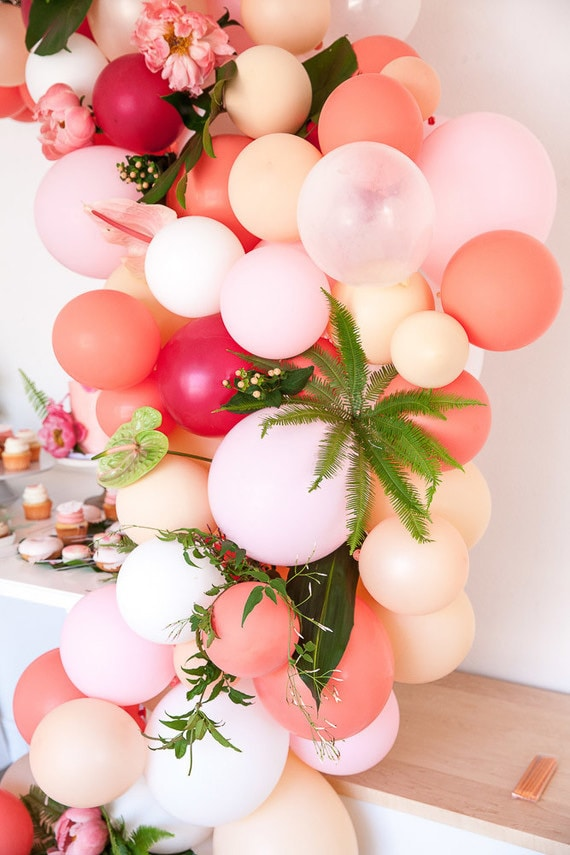 Coral, pink and peach balloon installation for dessert table featuring tropical plants | Kayla Plouffe via 100 Layer Cakelet