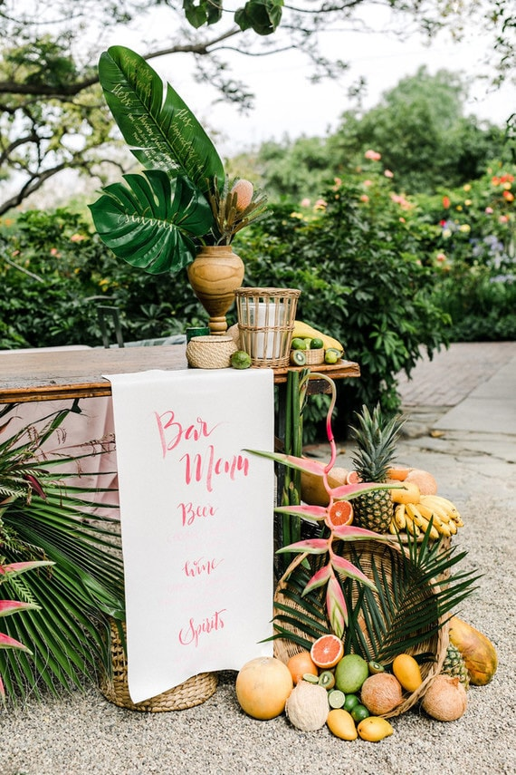 Bright tropical wedding bar with palm leaves and fruit | Anna Delores Photography via 100 Layer Cake