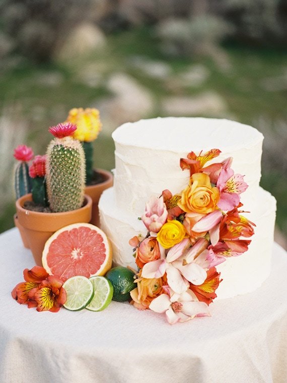 Tropical wedding cake topped with bright coral, pink and yellow flowers styled with potted cacti and citrus fruits | Chelsea Scanlan via Ruffled