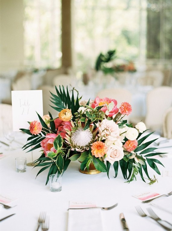 Tropical wedding centrepiece with palm leaves, protea and peony in coral, orange, pink and yellow | Hannah Mayson Photo via 100 Layer Cake