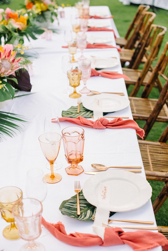 Tropical wedding reception place settings with peach and yellow coloured glassware, palm leaves, gold cutlery and bright coral napkins | Krista Mason Photography via Ruffled