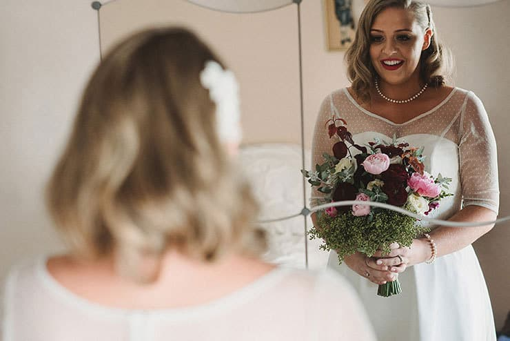 Bride looking in mirror with bouquet