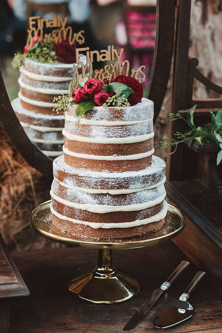 Naked wedding cake with wooden topper and flowers