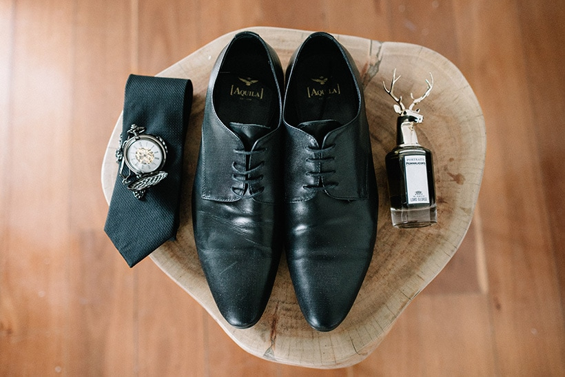 Groom accessories on wedding day including black leather shoes, cologne, tie and pocket watch | Nattnee Photography