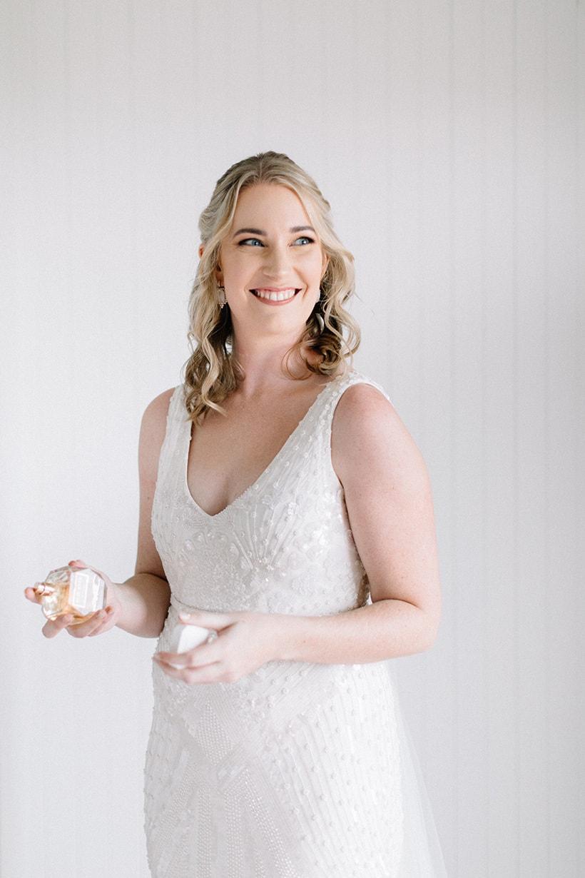 Bride in beaded ivory wedding dress spraying signature perfume | Nattnee Photography