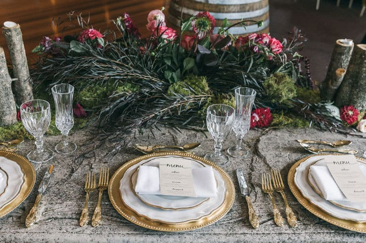 Bridal table place setting with gold chargers and cutlery