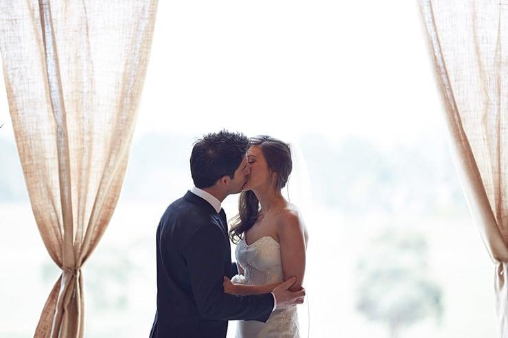 Winter-Barn-Wedding-Ceremony-Bride-Groom-Kiss